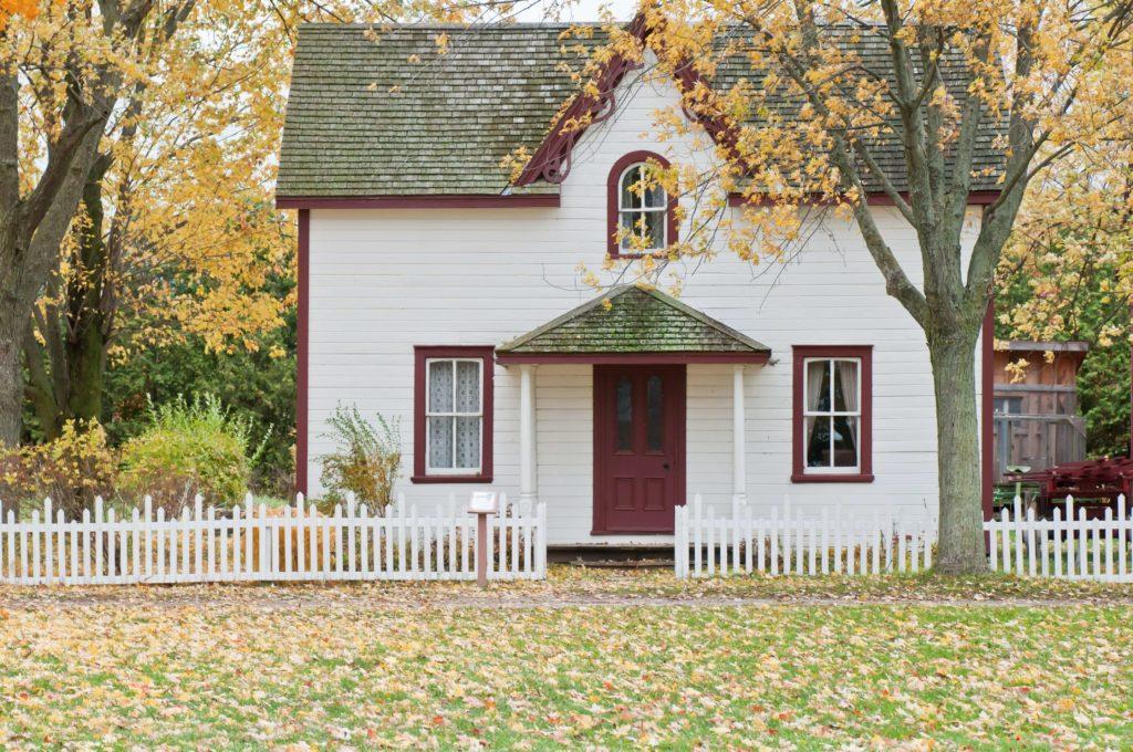 white wooden cottage in autumn