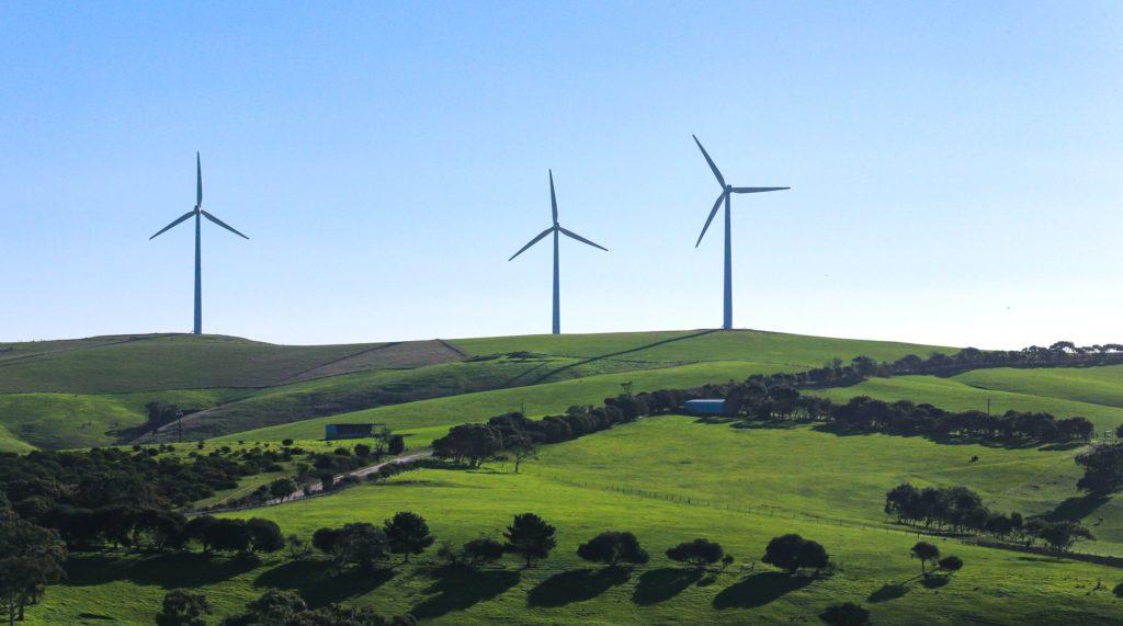 Wind turbine energy system on green hills