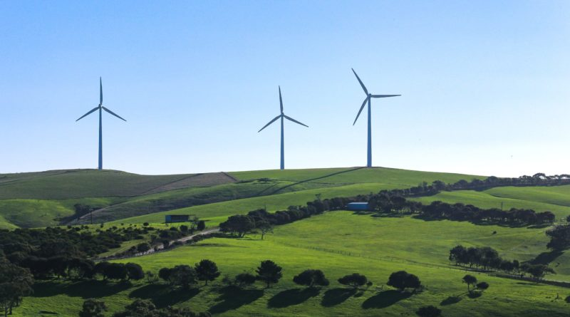 Wind turbine energy system on green hills